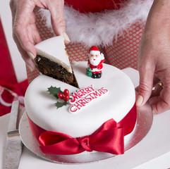 Santa's helper cutting slice of Christmas cake
