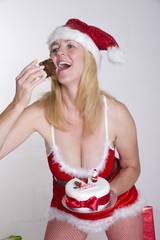 Woman in Santa outfit eating Christmas cake