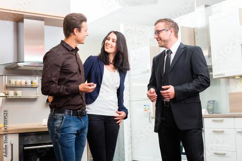Leinwanddruck Bild Verkäufer berät Paar bei Küchen Kauf im Möbelhaus