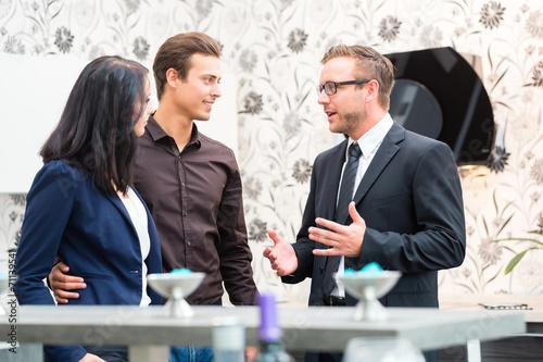 Verkäufer berät Paar bei Küchen Kauf im Möbelhaus - 71139541