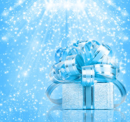 Gift box in blue wrapping paper on a beautiful abstract backgrou