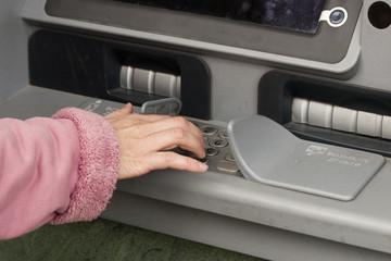 Женская рука набирает PIN код на клавиатуре банкомата