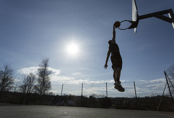 Silhouette basketball player slam dunking outdoors