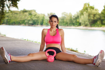 Attractive female sitting on the street with kettlebell