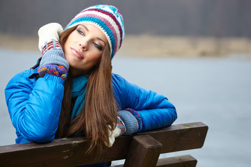 Smiling beautiful young woman relaxing outdoor in a winter day