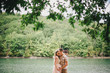 Young pregnant woman with her husband standing near lake