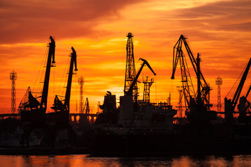 Silhouettes of cranes and cargo ships in port of Varna at sunset