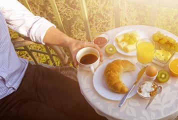 Mann mit Kaffeetasse am Frühstückstisch im Freien