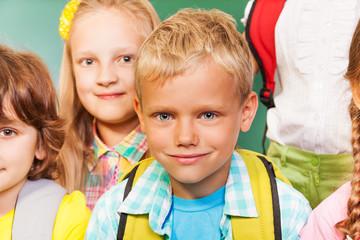 Happy children stand together near  blackboard