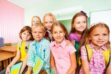 Schoolchildren sitting close near desk and smile
