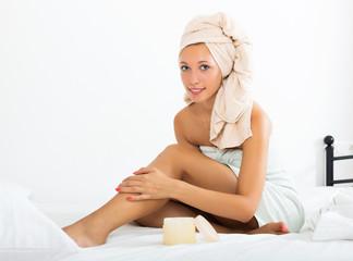Girl applying cream on legs