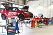 Leinwandbild Motiv Reifenwechsel in einer KFZ Werkstatt // Tire change by mechanic