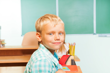 Smiling boy sits at desk with blackboard behind