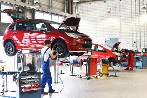 Leinwanddruck Bild Reifenwechsel in einer KFZ Werkstatt // Tire change by mechanic