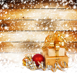 Snow-covered wooden wall with a beautiful gift box and bow
