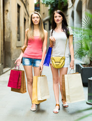 Two pretty young girls walking with shopping bags