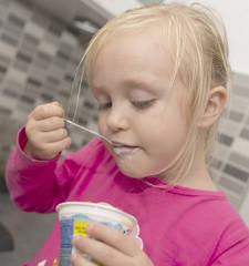 petitie fille mangeant yaourt