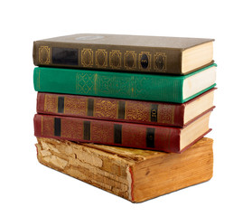 A stack of old books with gold stamping on a white background is