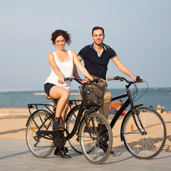 Two persons cycling on a city beach