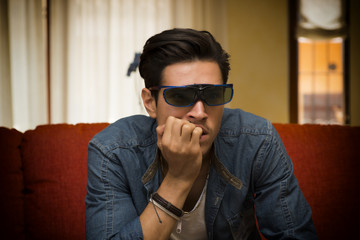 Young man wearing 3d glasses sitting watching a video