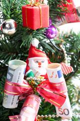 dekorierter Weihnachtsbaum mit Geldscheinen und Nikolaus