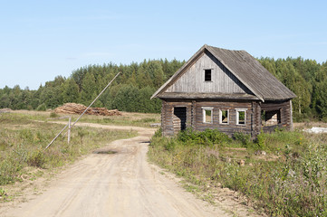 Dirt road and abandoned wooden house