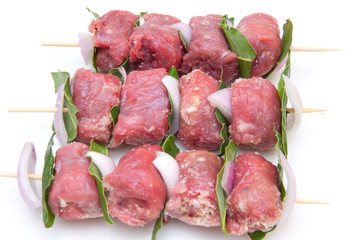 Skewers of meat on white background