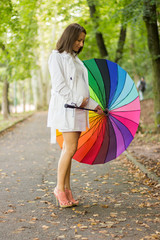 Happy pregnant woman under colorful umbrella in the rain
