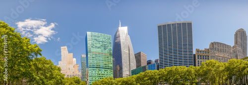 canvas print picture Modern skyscrapers surrounded by park trees under a beautiful bl