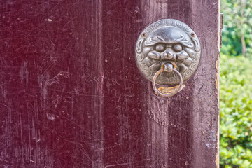 The art of a door knocker on red Chinese temple wooden door