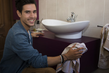 Cheerful young man cleaning the bathroom