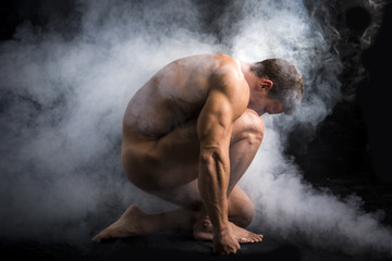 Handsome Nude Muscle Man Crouching in Fog in Studio