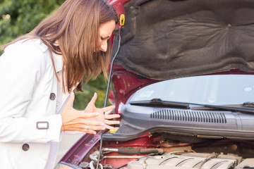 Worried young woman with her broken car