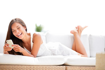 Smartphone woman using app smiling happy in sofa