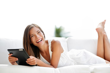 Tablet computer - young woman laughing in sofa