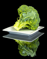 Broccoli head reflection on a square plate