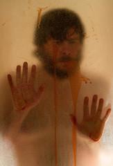 Man hiding behind a shower door.