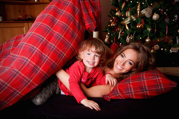 Beautiful young woman with a little girl at Christmas