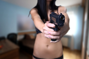 girl with a gun aiming for a thief at home