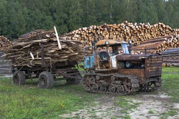 Старый трактор вывозит отходы лесопиления с пилорамы
