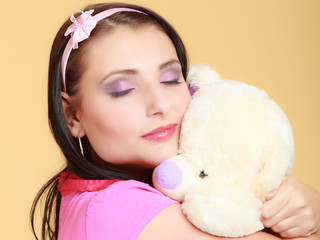 Childish infantile girl in pink hugging teddy bear toy