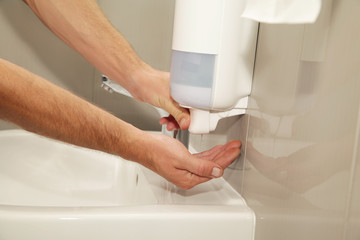 Male hands with soap dispenser use in the restroom