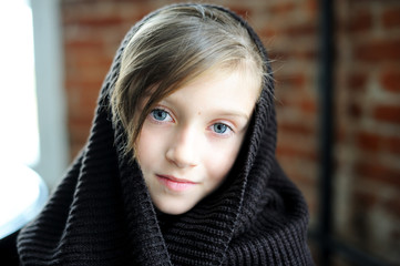 Kid girl in knitted snood on brick wall background