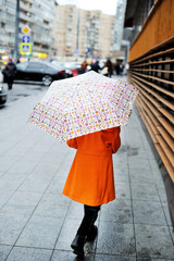 Colorful kid girl with umbrella on city street