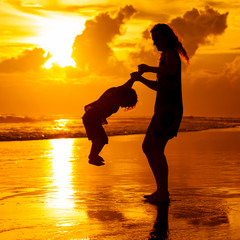 mother and  son playing on the beach at dawn time
