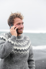 Smartphone man talking on phone on beach, Iceland