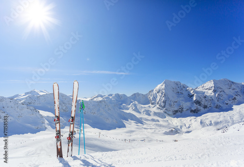 canvas print picture Skiing , mountains and ski equipments on ski run