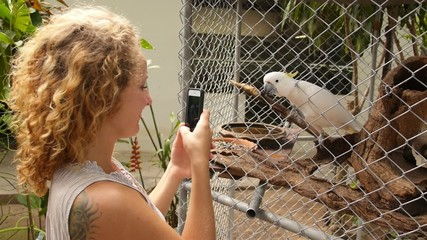 Blonde Girl Taking Picture by Cellphone of Cockatoo. Slow Motion