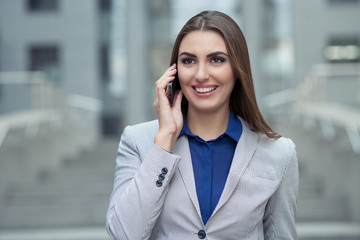 business woman talking on a cell phone on the background of the