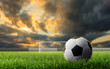 soccer ball on green grass with sunset background.